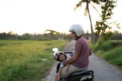 Fahter e sua criança apreciam montar o 'trotinette' da motocicleta foto de stock