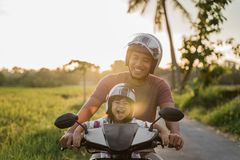 Fahter ed il suo bambino godono di di guidare il motorino del motociclo fotografia stock