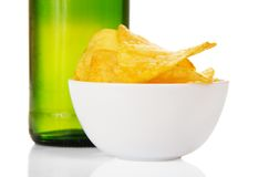 Faience bowl with chips and wet bottle of beer Royalty Free Stock Photos