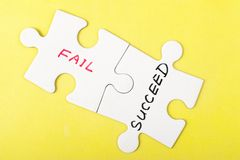 Fail or succeed. Words on two pieces of jigsaw puzzle Stock Photos