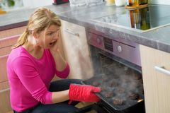 Failed cooking in kitchen. Middle aged woman failed cooking in kitchen Stock Photography