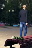 Failed dating. Man walks away. Close up white broken rose on the bench stock images