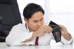 Failliet, brak en frustreerde de mens heeft financiële problemen met muntstukken verlaten op de lijst en een lege portefeuille royalty-vrije stock fotografie
