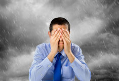 Failure in the business. Portrait of businessman worried with hands on his face and the storm in the background royalty free stock images
