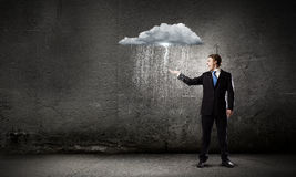 Failure in business. Young businessman under raining sky. Failure concept Stock Images