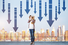 Failure concept. Young woman covering head with book while standing on concrete rooftop with railing, city view and downward arrows. Failure concept Stock Photo