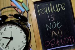 Failure Is Not An Option on phrase colorful handwritten on chalkboard. And alarm clock with motivation, inspiration and education concepts. Table background royalty free stock image