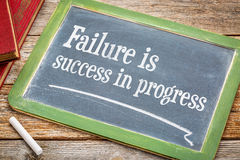 Failure is success in progress. Inspirational text on a  slate blackboard with a white chalk and a stack of books against rustic wooden table Stock Photography