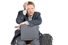 Failure traveling businessman. Traveling businessman or salesman with laptop and luggage waiting in an airport lounge, in a depressed, pondering and unhappy Royalty Free Stock Photography