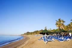 Fainéants de Sun sur une plage sablonneuse à Marbella Image stock