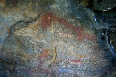 FAINT ANCIENT BUSHMAN DRAWINGS IN EASTERN FREE STATE AGAINST A ROCK WALL. View of ancient bushman drawings on the interior wall of a rock cave stock photography