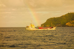 A faint rainbow over a cargo ship in the caribbean Royalty Free Stock Photo