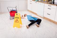 Fainted Housemaid Lying On Floor In Kitchen. Young Fainted Housemaid Lying On Floor In Kitchen. Accident Compensation Concept Stock Photo