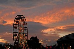 The fair. A carnival ride light up at sunset at a Maine fair stock photography