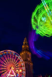 Fair in the city at night time. With church on the background Royalty Free Stock Image