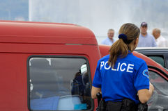 A fair cop. A female gendarme questions a motorist in an old, beat-up van as onlookers watch from a distance. Space for text in the sky above the van Royalty Free Stock Image