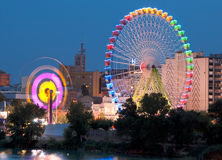 Fair Ferris wheel adorned with lights spinning Stock Photo