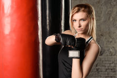 Fair-haired athletic girl standing beside the punch bags in a gym decorated in white, black and red colors. Royalty Free Stock Images