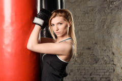 Fair-haired athletic girl working out in a gym decorated in loft style, leaning on a red punching bag. Royalty Free Stock Photos