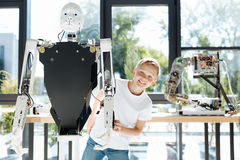 Fair-haired boy emerging from behind a human robot royalty free stock images