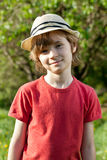 The fair-haired boy in red shirt and hat Royalty Free Stock Image