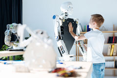 Fair-haired boy touching chest of a human robot royalty free stock photo