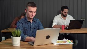 Boy Takes a Break. Fair-haired caucasian boy with lovely blue eyes taking a break, wearing casual denim shirt, relaxing at office brown desk stock video footage