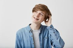 Fair-haired dreamy hipster guy imagines something in his mind, looks aside, smiles, being deep in thoughts, scratching. Portrait of pensive fair-haired dreamy Stock Images