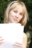 Fair-haired girl with with blank papers. Fair-haired girl holding blank papers looking to camera Stock Photos