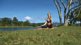 Girl Sits in Yoga Pose on Grass at Tree near River. Fair-haired girl sits in yoga pose Padmasana on green grass at bare tree trunk near calm river in countryside stock video