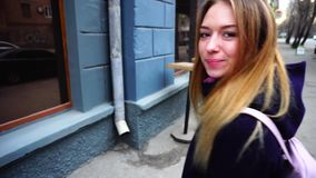 Fair haired girl walking on street and smile. Lady with long healthy hair walking on street, in close-up photography. Woman dressed in black coat and backpack stock footage