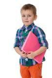 Fair-haired little boy holding under his arm a Stock Photos