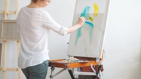 Fair-haired woman painting with a brush. In the art classes. Hobby, lifestyle, free time stock footage