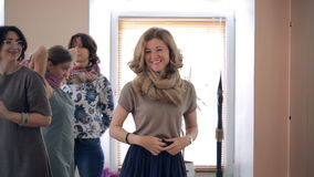 Fair-haired woman ties scarf on style lesson inside studio. Blonde smiling female in beige blouse, blue skirt, wearing brown tissue. Brunette stylist explains stock video footage