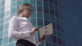 Fair-haired young business woman using het tablet to work outdoors. Fair-haired young business woman standing at the entrance of business center and using het stock video