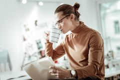 Fair-haired young designer from fashion school in black shoes having coffee. Coffee break. Fair-haired young designer from fashion school in black shoes having royalty free stock image