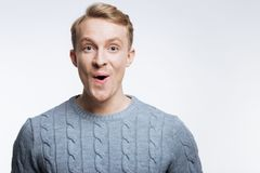 Fair-haired young man looking surprised. This is unbelievable. Handsome fair-haired man in a grey sweater looking at the camera with a surprised expression while stock photo