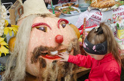 Fair. Halloween. Girl examines and touches pumpkin dressed up as a man's head. Royalty Free Stock Image