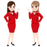 Fair Hostess Women. Two beautiful professional fair hostess women standing with red uniform smiling happy Stock Photo