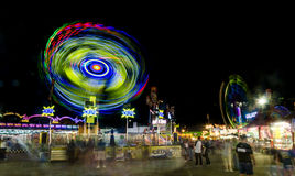 Fair Motion. This was shot at the Arizona State Fair in Phoenix.  I used a long exposure to bring out the motion of the rides and People Royalty Free Stock Photos