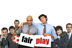 Fair play. Team of  businessmen with soccer ball and white cards with the words fair play isolated in white Royalty Free Stock Photography