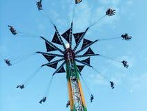 Fair rides. Swings at fair with sunset Stock Photos