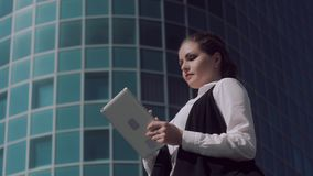 Fair-skinned attractive business woman working on the tablet outdoors. Against office center background stock video