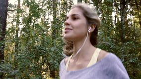 Fair-skinned woman jogging in the park on a sunny day. Slow motion stock video