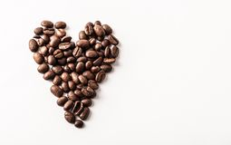 Fair trade roasted organic coffee beans shaped as a heart on whi. Te background - Concept of caffeine love, breakfast, decaf or morning contentment - Coffee shop royalty free stock photography