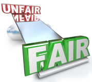 Fair Vs Unfair Words Balanced on Scale Justice Injustice. The words Fair and Unfair balanced on a see-saw, balance or scale to symbolize justice versus injustice Royalty Free Stock Photography