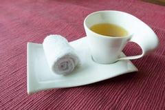Faire bon accueil à la station thermale thaïlandaise chaude roulée de thé d'herbe de serviette humide Image stock