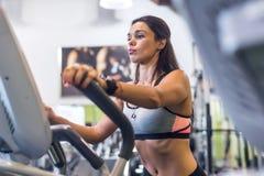 Faire convenable de femme cardio- dans un entraîneur elliptique dans un gymnase Photos libres de droits