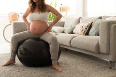 Faire de femme enceinte détendent des exercices avec un fitball Photographie stock