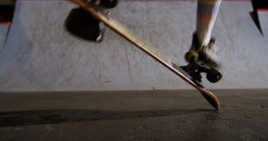 Faire de la planche à roulettes de pratique d'homme dans l'arène 4k de planche à roulettes banque de vidéos